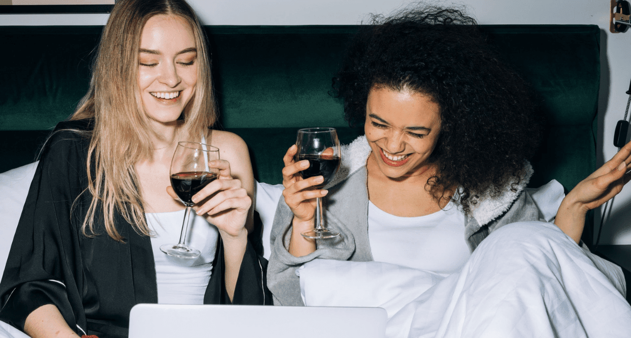 Two women drinking red wine in bed and laughing at something on a laptop