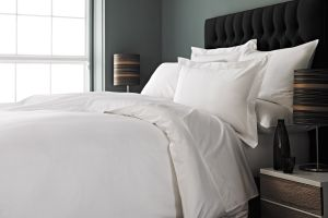 Duvet and pillows on bed against black headboard