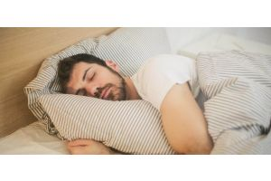 Man sleeping with striped duvet cover