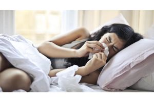 Woman lying on bed and blowing nose due to allergies